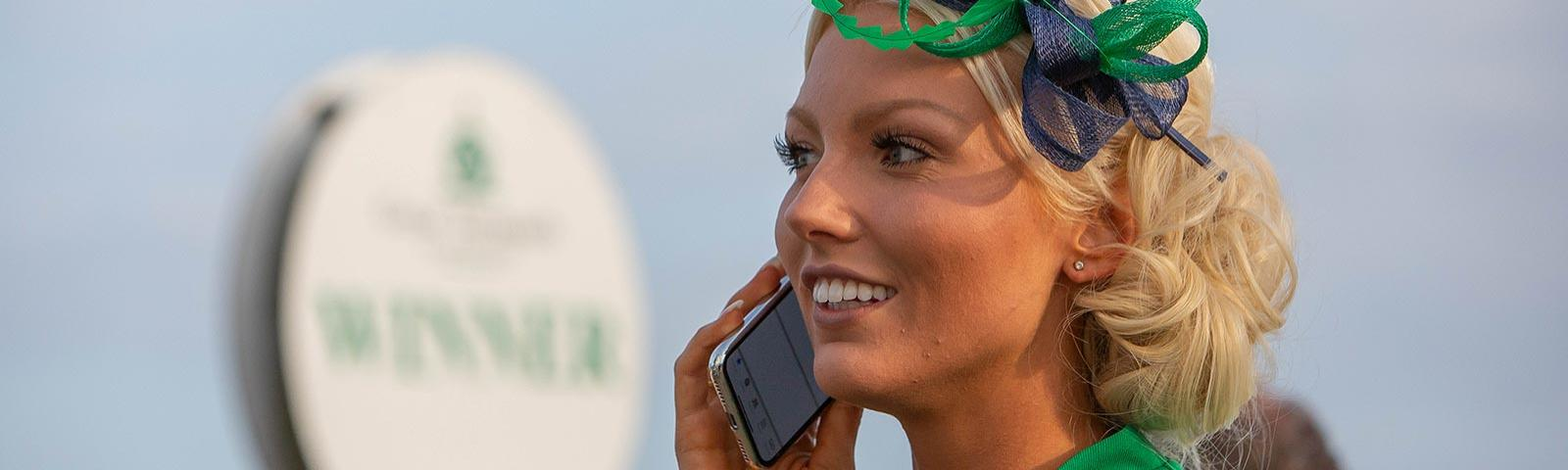 A dressed up woman making a phone call while at the races.