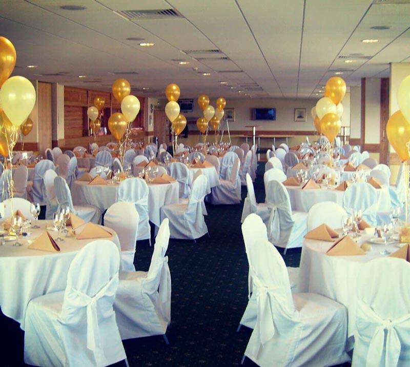 Dressed tables with golden balloons are laid out for a party