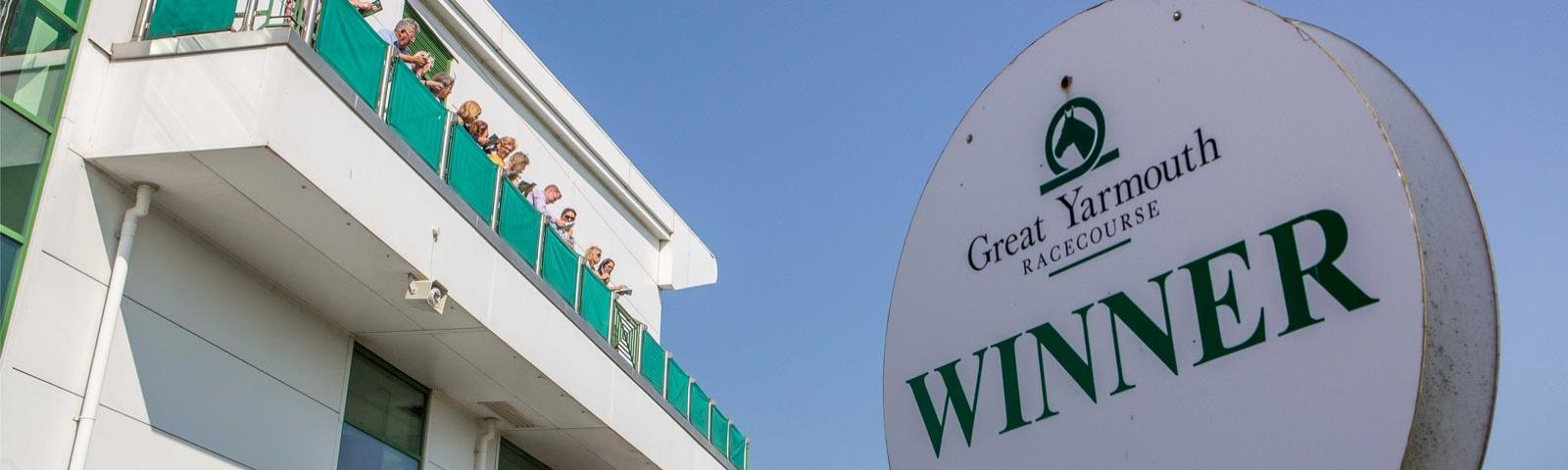 Close up on a winners sign with the grandstand in the background at Great Yarmouth Racecourse.