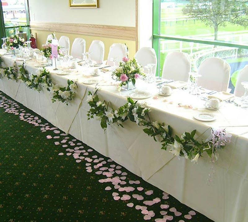 A clothed table decorated for a wedding