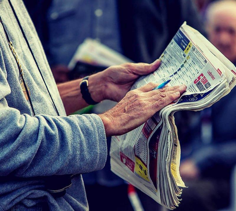 Racegoer reading through a newspaper.