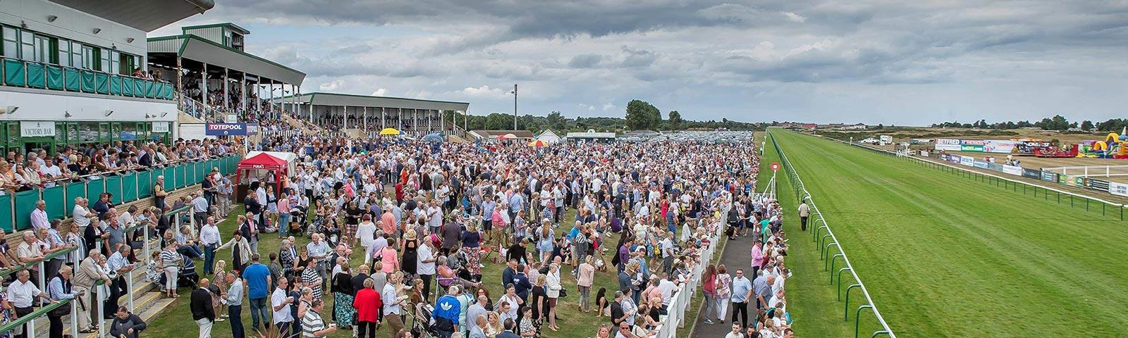 a large crowd of people gather at a racecourse