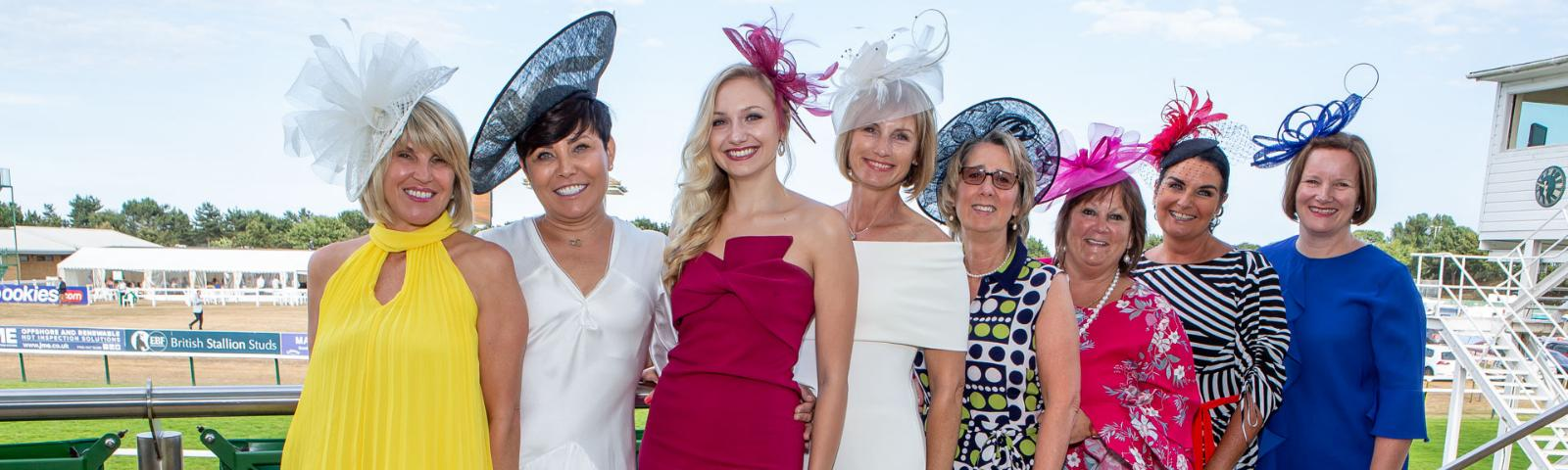 A group of well dressed Ladies pose for the camera on Ladies Day at Great Yarmouth Racecourse.